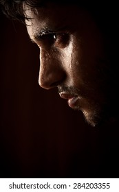 Close up portrait of a handsome indian young angry man sweating over dark background