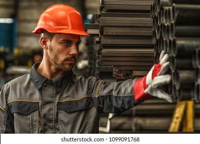 Close up portrait of a handsome male industrial engineer wearing protective helmet checking steel supplies at the storage of manufacturing company copy space. Job, heavy industry, occupation