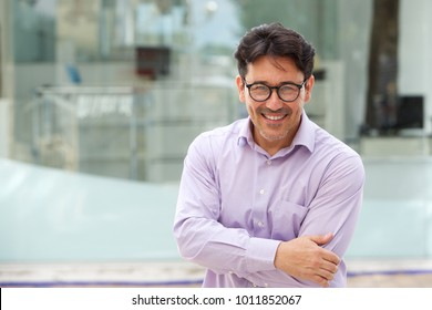 Close up portrait of handsome man in glasses standing with arms crossed outdoors and smiling