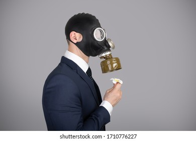 Close up portrait of handsome man in a protective gas mask, virus protection concept. Holding a plumeria flower in his hand and sniffing through a gas mask