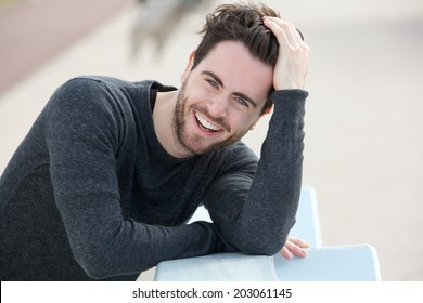 Close up portrait of a handsome man smiling with hand in hair