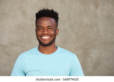Close up portrait of handsome man smiling and standing by wall