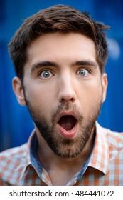 Close up portrait of handsome man surprised over blue background.