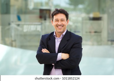 Close up portrait of handsome mature man in business suit posing with arms crossed outdoors and smiling