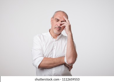 Close up portrait of handsome mature man in white shirt holding hand near face and thinking about work or life problem. Concept of being nervous and exhausted