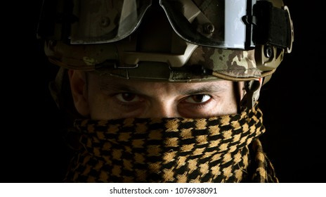 close up portrait of handsome military man. Macro shot on black background in scarf on face
