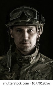 close up portrait of handsome military man. Macro shot on black background looking at camera