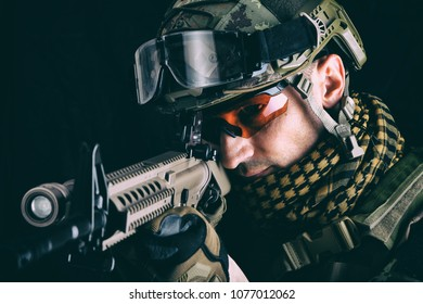 close up portrait of handsome military man. Macro shot on black background sniper with automatic rifle aiming and shooting