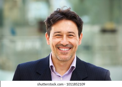 Close up portrait of handsome older man in suit with big smile on his face