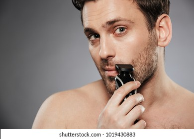 Close up portrait of a handsome shirtless man shaving beard with an electric razor isolated over gray background