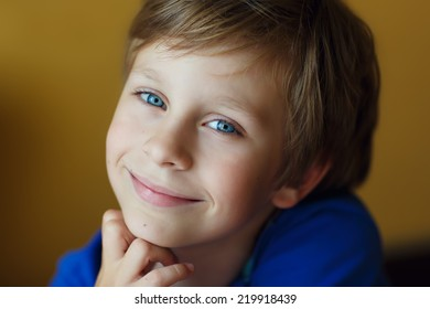 A close up portrait of a handsome smiling little boy with blue eyes