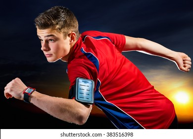 Close up portrait of handsome teen sports man with activity app on digital devices. Young man wearing armband with smart phone and smart watch against sunset background.