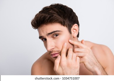Close up portrait of handsome unhappy sad upset brunette brown-haired with stubble young guy trying to squeeze out pimple rash with fingers isolated on gray background