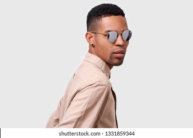 Close up portrait of handsome young African American man wearing round mirror sunglasses and casual beige shirt, looking to the camera and posing over white studio background. People emotion concept