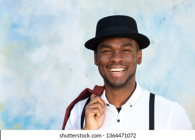 Close up portrait of handsome young african american man with suspenders and hat smiling by wall