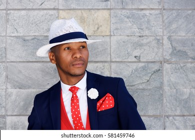 Close up portrait of handsome young african man in suit and hat looking away and thinking