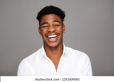 Close up portrait of handsome young black man laughing against gray background