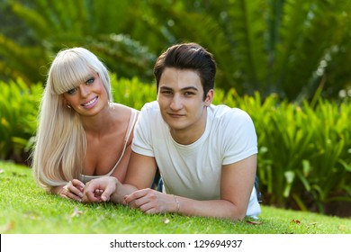 Close up portrait of handsome young couple laying on green grass in park.