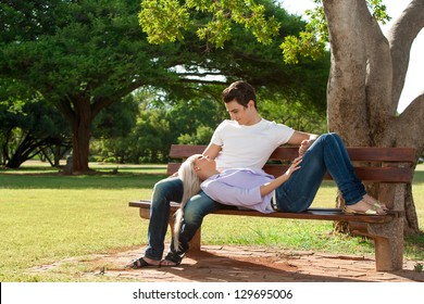 Close up portrait of handsome young couple relaxing on wooden bench in park.