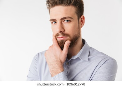 Close up portrait of a handsome young man dressed in shirt holding hand on his chin isolated over white background