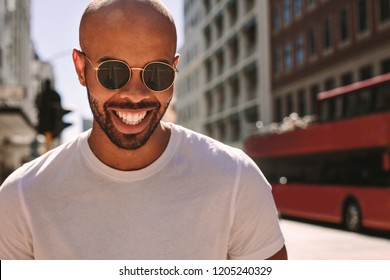 Close up portrait of handsome young man wearing sunglasses walking down the street and smiling. African man being a tourist in a big city.