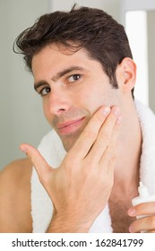 Close up portrait of a handsome young man applying moisturizer on his face