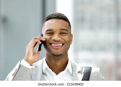 Close up portrait of a handsome young man smiling with mobile phone