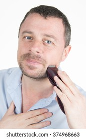 Close up portrait of a handsome young man using an electric shaver, isolated on white background