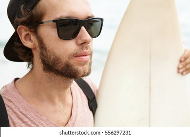 Close up portrait of handsome young man with fuzzy beard wearing sunglasses and baseball cap backwards holding his white surfboard and looking at ocean, waiting for giant waves to practice new tricks