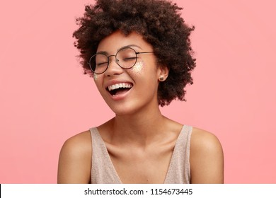 Close up portrait of happy African American female laughs at something funny, has positive expression, wears glasses, has curly hair, dressed casually, closes eyes with happiness, isolated on pink