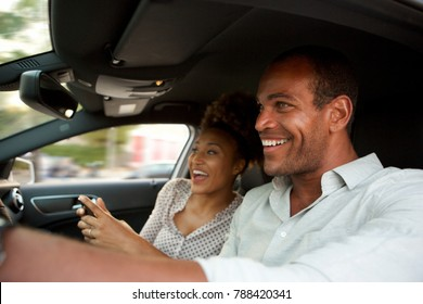 Close up portrait of happy African American couple in fast car smiling
