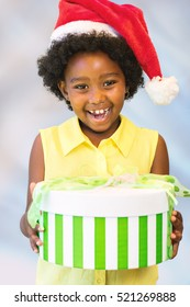 Close up portrait of happy african kid holding christmas gift boxes.Girl wearing red hat against light blue background.