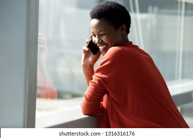 Close up portrait of happy african woman talking with cellphone by window
