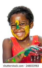 Close up portrait of happy African youngster with painted face.Isolated against white background.