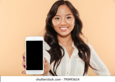 Close up portrait of a happy asian woman showing blank screen mobile phone isolated over beige background