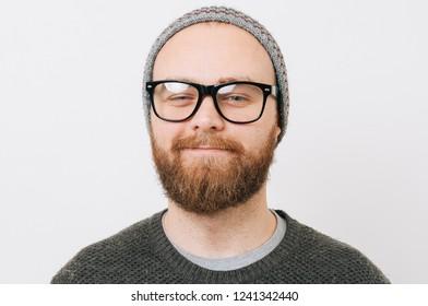 Close up portrait of happy bearded man wearing eyeglasses over white background