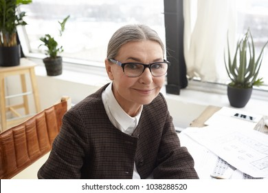 Close up portrait of happy beautiful 60 year old experienced female chief architect wearing jacket and eyeglasses doing paperwork in office, smiling joyfully at camera, enjoying her occupation