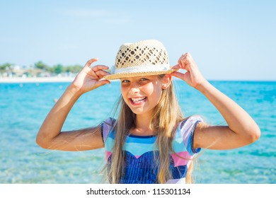 Close up portrait of happy beautiful girl in the beach hat relax near the sea