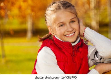 Close portrait of happy blond 11 years old girl with amazing smile sitting  on the bench 36dd478e8139f