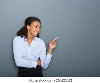 Close up portrait of a happy business woman pointing finger on gray background