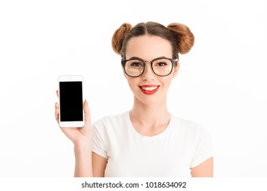 Close up portrait of a happy casual girl showing blank screen mobile phone isolated over white background