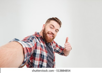Close up portrait of a happy casual man taking selfie and showing thumbs up gesture over white background