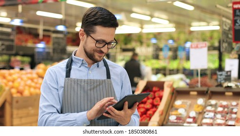 Close up portrait of happy Caucasian male worker in glasses standing in supermarket and typing on tablet. Young joyful man food store assistant at work tapping on device indoors. Retail concept