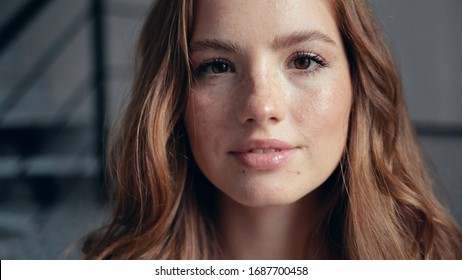 Close up portrait of happy charming young woman with golden hair and freckles looking at camera feel happy the light wind blows