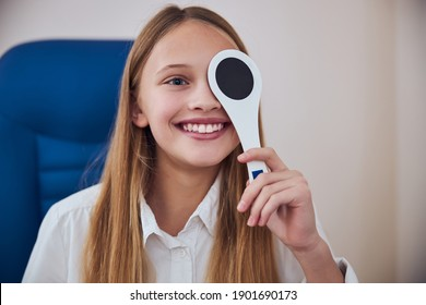 Close up portrait of happy cheerful blonde Caucasian female child sitting in blue medicine chair while checking eyesight in ophthalmologist clinic