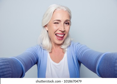 Close up portrait of happy cheerful delightful charming beautiful flirty mature lady granny grandma, she is giving a wink, showing a tongue and taking a selfie on vacation, isolated on gray background