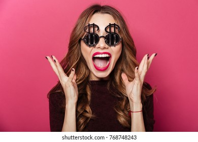 Close up portrait of a happy cheerful girl wearing dollar shaped sunglasses screaming isolated over pink background