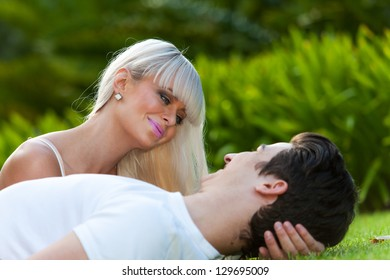 Close up portrait of happy couple laying on grass outdoors.