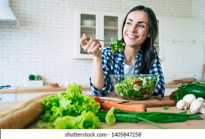 Close up portrait of happy cute beautiful young woman while she try tasty vegan salad in the kitchen at home. Healthy lifestyle. Good life. Organic food. Vegetables.