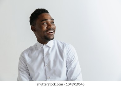 Close up portrait of a happy excited young african american man laughing against gray background.